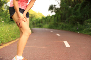 woman runner hold her sports injured legs