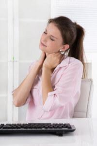 Frau sitzt mit Schmerzen im Nacken im Büro