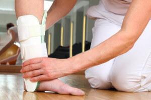 Ärztin oder Therapeutin beim Anlegen einer Knöchelbandage